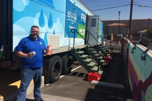 Man in a blue shirt standing beside a 'Clean the World: Fresh Start Mobile Showers' truck
