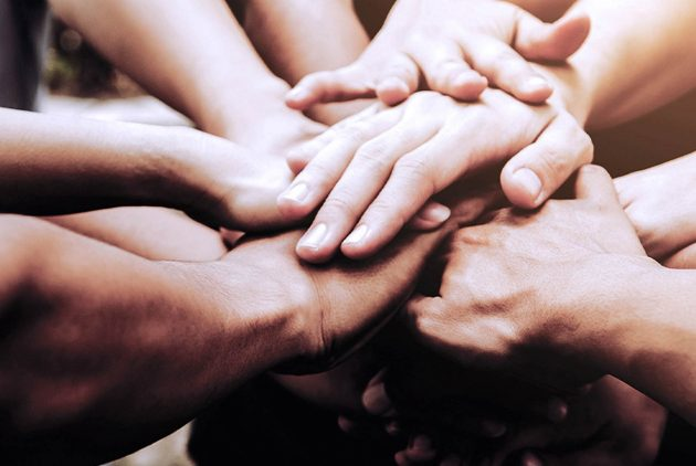 Image of a team with hands in a circle